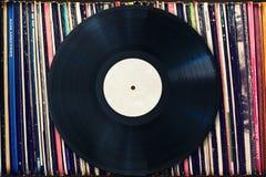 Disque vinyle avec l'espace de copie devant une collection d'albums, processus de vintage Photographie stock libre de droits