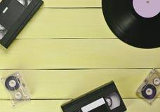 Disque vinyle, cassette vidéo, cassette sonore sur un Ba en bois bleu photographie stock