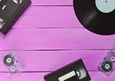 Disque vinyle, cassette vidéo, cassette sonore sur un Ba en bois bleu image stock