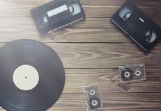 Disque vinyle, cassette vidéo, cassette sonore sur un backgr en bois image stock