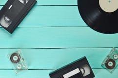 Disque vinyle, cassette vidéo, cassette sonore sur un fond en bois bleu Vue supérieure Rétro technologie de media, l'espace de co photo libre de droits