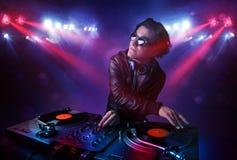Disques de mélange du DJ d'adolescent devant une foule sur l'étape images libres de droits