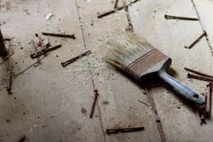 Disrepair. An old paintbrush that is losing it's bristles covered with dust and rust surrounded by rusty nails Royalty Free Stock Images