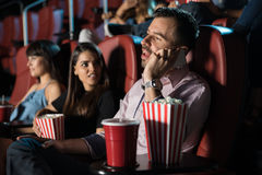 Disrespectful man in a movie theater. Profile view of a very obnoxious and disrespectful men talking on the phone while sitting in a movie theater stock image