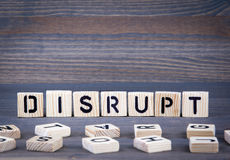 Disrupt word written on wood block. Dark wood background with texture Stock Images