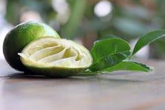 Disséquez la chaux est serrent avec la pleine chaux et les feuilles sur la table en bois Image libre de droits