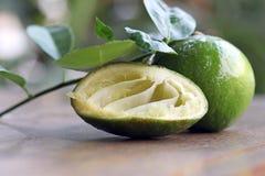 Disséquez la chaux est serrent avec la pleine chaux et les feuilles sur la table en bois Photo libre de droits