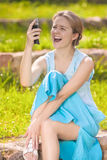Dissapointed and Angry Young Caucasian Woman Shouting at Her Cel. Lphone. Sitting on the Ground Against Green Grass. Vertical Image Composition Royalty Free Stock Image