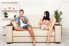 Dissapointed beautiful brunette woman in quarrel with her boyfriend. Indifferent man watching TV. Dissapointed beautiful brunette women in quarrel with her Stock Image