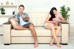 Dissapointed beautiful brunette woman in quarrel with her boyfriend. Indifferent man watching TV. Dissapointed beautiful brunette women in quarrel with her Royalty Free Stock Photography