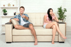 Dissapointed beautiful brunette woman in quarrel with her boyfriend. Indifferent man watching TV. Dissapointed beautiful brunette women in quarrel with her Stock Photo