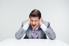 Dissapointed businessman sitting at the table. And covering his ears over gray background Stock Photography