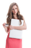 Dissapointed girl holding laptop and credit card. Dissapointed girl holding laptop and debit card. Empty credit card concept on white background Stock Image
