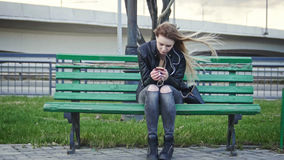 Dissapointed girl with long blonde hair in leather jacket straightens  use gadget sitting on the bench in the wind. Dissapointed girl with long blonde hair in Stock Image