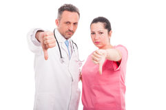 Dissapointed medical doctor and woman giving thumbs down. Dissapointed medical doctor and women giving thumbs down hand gesture isolated on white background Royalty Free Stock Photos