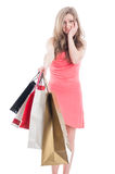 Dissapointed shopping young woman. Dissapointed young woman holding shopping bags on white background Royalty Free Stock Images
