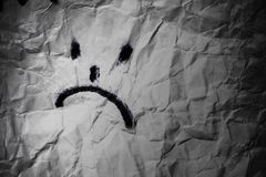 Dissapointed smile. Sad face on crumpled paper in dark background. Depression treatement concept Royalty Free Stock Photos
