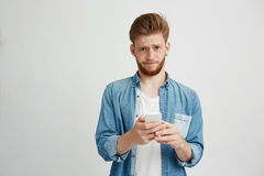 Dissapointed upset young man with beard holding smart phone looking at camera over white background. Copy space Stock Photography