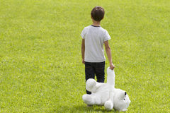 Dissapointed young boy is holding a teddy bear and standing on the meadow. Child looking down. Back view. Sadness, fear. Disappointed boy is holding a teddy bear stock images
