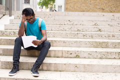 Dissapointed. Young man reading a letter in the street Royalty Free Stock Image