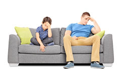 Dissappointed brothers sitting on a sofa Stock Photo