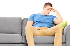 Dissappointed young man sitting on a couch Royalty Free Stock Photo