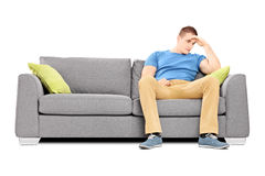 Dissappointed young man sitting on a sofa Royalty Free Stock Photos