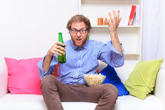 Dissatisfacted man on the couch when watching TV Royalty Free Stock Photos