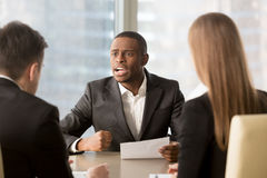 Dissatisfied african-american boss clenching fist, scolding empl Royalty Free Stock Photography