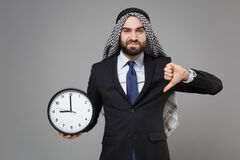 Dissatisfied bearded arabian muslim businessman in keffiyeh kafiya ring igal agal classic suit isolated on gray