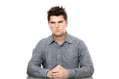 Dissatisfied boss. A portrait of a young dissatisfied boss sitting in his office against white background stock image