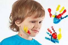 Dissatisfied boy with painted face on background of hand prints Royalty Free Stock Photo