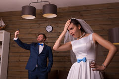 Dissatisfied bride and groom making selfie Royalty Free Stock Photos