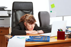 Dissatisfied business lady. At a busy desk with her head resting on her hands royalty free stock photography