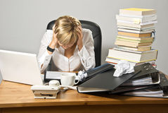 Dissatisfied Business Lady. Or student sitting at a busy desk stock photo