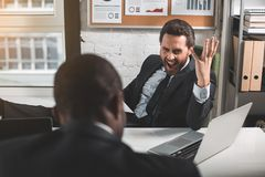 Dissatisfied businessman is yelling at his subordinate. Feeling annoyed. Portrait of irritated young bristled boss is sitting at table with his employee and Stock Photos