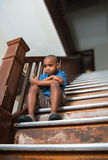Dissatisfied child. Sitting on a damaged wooden stair case Royalty Free Stock Photo