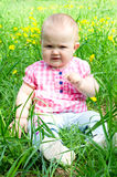 Dissatisfied child. Unhappy baby girl sitting on the green grass royalty free stock photo