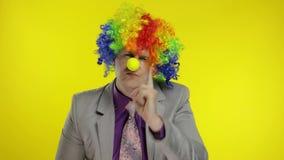 Clown businessman entrepreneur boss in wig quarrels and waves his finger at work