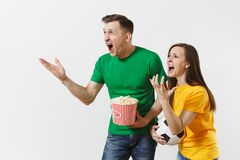 Dissatisfied couple, woman, man, football fans in yellow green t-shirt cheer up support team with soccer ball bucket of. Popcorn isolated on white background stock photos