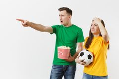 Dissatisfied couple, woman, man, football fans in yellow green t-shirt cheer up support team with soccer ball bucket of. Popcorn isolated on white background stock images