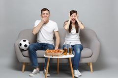 Dissatisfied couple woman man football fans cheer up support favorite team covering eyes mouth with palms isolated on. Dissatisfied couple women men football royalty free stock image