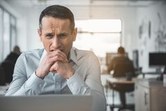 Dissatisfied employer in modern office. Portrait of worried businessman biting hand while using appliance during labor. Bad day in company concept Stock Photos
