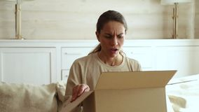 Dissatisfied female customer open cardboard box receive damaged parcel stock video footage