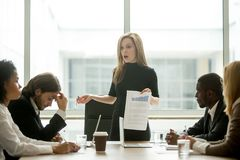 Dissatisfied female executive scolding employees for bad work at. Dissatisfied angry female executive scolding african employee for bad work at diverse group royalty free stock image