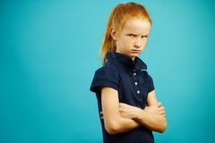 Dissatisfied girl with angry expression stands on isolated blue background, expresses frustration or dissatisfaction. Demonstrates bad mood, folded her hands Stock Photography