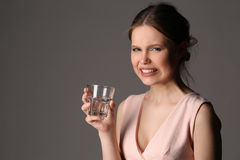 Dissatisfied girl with glass of water. Close up. Gray background Stock Photos