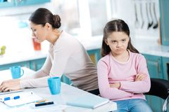 Dissatisfied girl and her mom working. Boredom. Sweet dissatisfied dark-eyed girl having her arms crossed and sitting near her mom working on her laptop Royalty Free Stock Photo