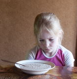 Dissatisfied girl with porridge plate Stock Photos