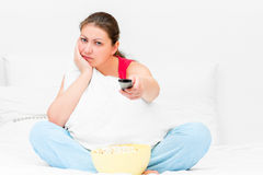 Dissatisfied girl  with a TV remote control Royalty Free Stock Photos